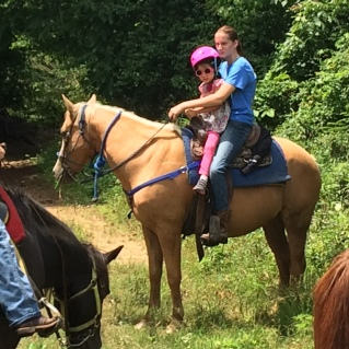 "Nat's first horse ride. Riding tandem with instructor on ""Nugget""."